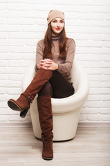 young girl sitting in a white round chair