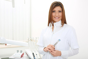 beautiful girl dentist with mirror and dental probe