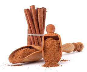 ground cinnamon spice powder in wooden spoon isolated on white b