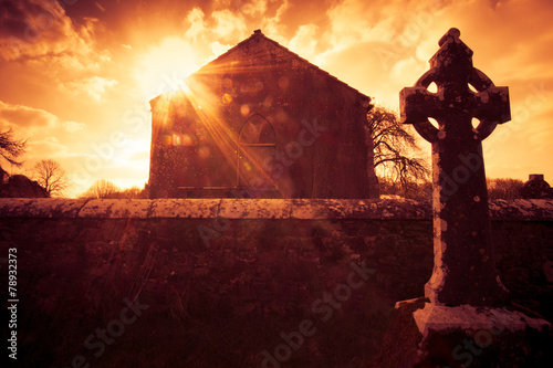 Ireland celtic cross at medieval cemetery under fiery sky - 78932373