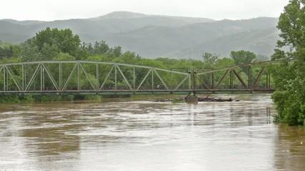 Old rail bridge across overflowing river flow,flood