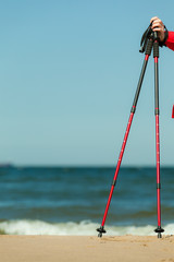 Nordic walking. Red sticks on the sandy beach