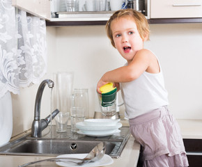 Small girl cleaning dishes