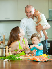 family of four together in the kitchen prepares seafood