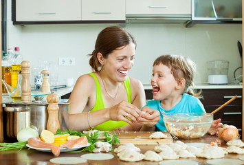 mother with her daughter makes  fish meatballs in home