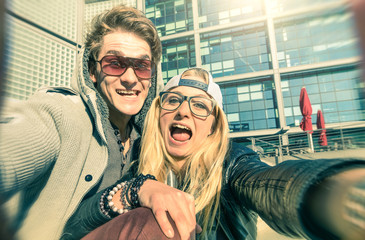 Young hipster couple in love taking selfie in urban area