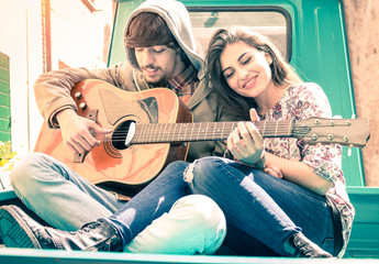 Romantic couple of lovers playing guitar on old fashioned car