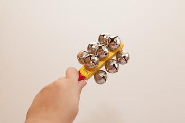 Hand holding jingle stick horizontally