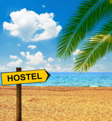 Tropical beach and direction board saying HOSTEL