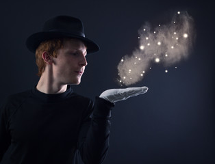 young magician in a black hat and white gloves