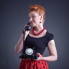 Cheerful woman talking on land line phone.