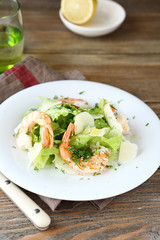 Delicious salad with shrimps, lettuce and cheese on a plate