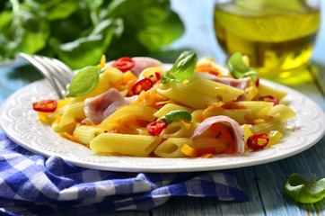 Photo : Penne with fried vegetable and smoked bacon.