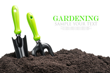 garden tools in soil isolated on white