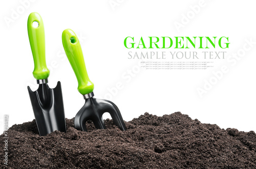 Leinwanddruck Bild garden tools in soil isolated on white