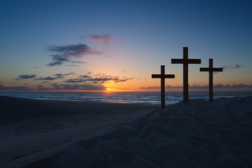 Three crosses on sand dune next to the ocean with a cloudy sunri