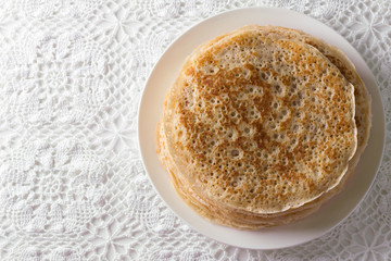 Plate with homemade yeast pancakes on a lace tablecloth