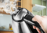 Stainless Steel Electric Kettle in hand on the background of the