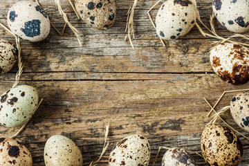 Easter - quail eggs with hay on an old vintage wood from above