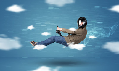 Funny racedriver young man driving between clouds concept
