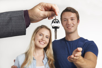 Dealer Handing Over Keys For New Car To Young Couple