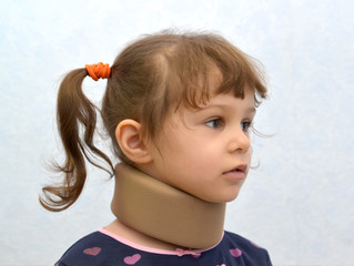 Portrait of the little girl with an orthopedic collar of Chance