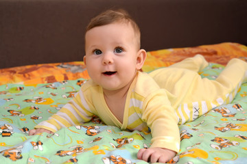 The cheerful baby lies on a stomach