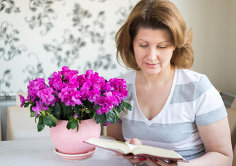 Woman reading a book while sitting at  table