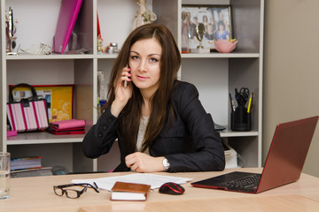 Business woman at the office conducts a dialogue by phone