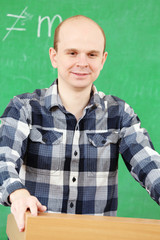Teacher near chalkboard in classroom
