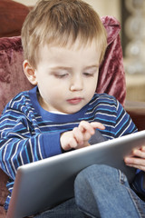 Boy Sitting On Sofa And Playing With Digital Tablet