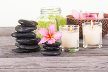 Spa with green bath salt, black stones and flowers