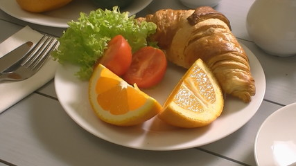 Breakfast with croissant, tomato end tea