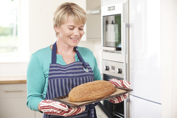 Woman Holding Tray With Home Made Loaf Of Bread