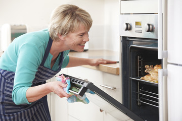 Woman Looking At Chicken Roasting In Oven