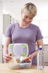 Woman Preparing Healthy Lunchbox In Kitchen