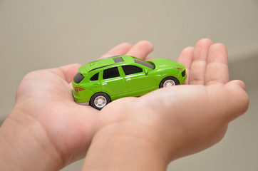 Green toy car on a right hand