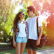 Sunny portrait of happy young couple teenagers in urban style