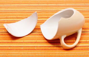 Broken mug, shattered cup on orange cloth