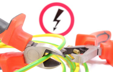 Metal pliers, green yellow cable and high voltage danger sign