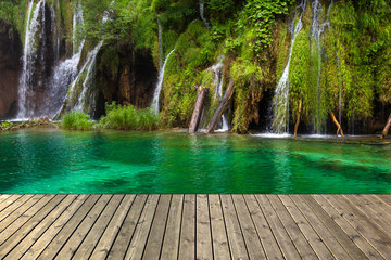 Waterfall in Plitvice lake and wooden plank, Croatia.