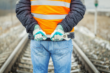 Worker hands with adjustable wrench on the railroad