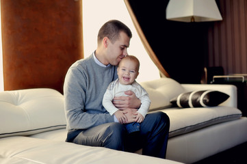 in the room sitting on a white sofa happy father with his young