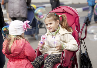 a child in a wheelchair in the Park soap bubbles