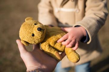 熊の縫い包みを手渡す親子
