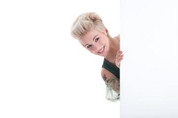 Sympathische Frau im Dirndl blickt hinter Wand hervor