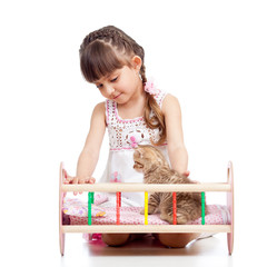 kid playing with a kitten and rocking him in doll crib