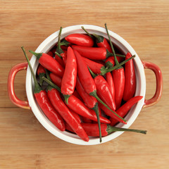 Red thai chili peppers in red bowl on wood background