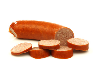 cut smoked sausage with some pieces on a white background
