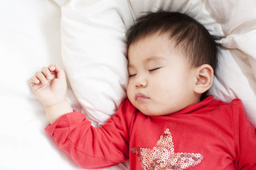 One baby girl sleeps alone with white blanket and sheet close up